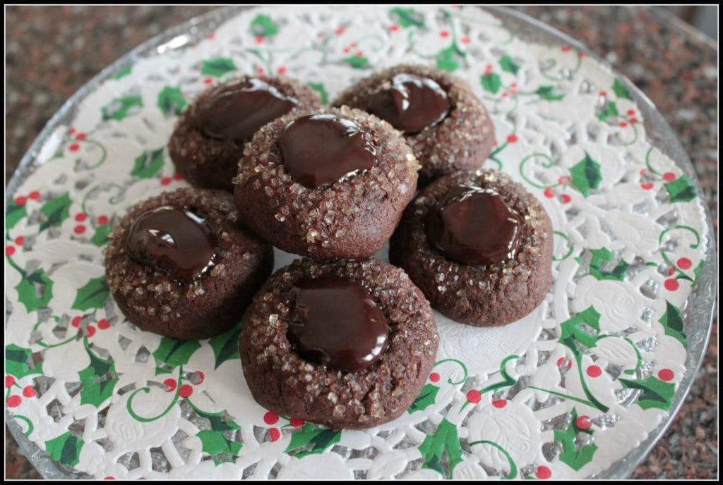 Bailey's Thumbprint Cookies A plate full of dark chocolate cookies topped with crystal sugar and chocolate ganache.