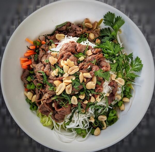 A white bowl filled with Vietnamese beef noodle salad.