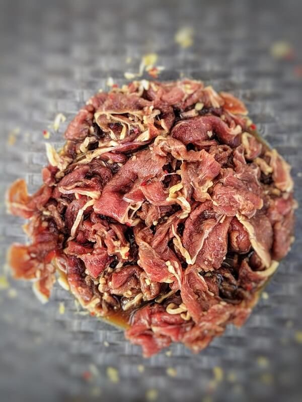 A bowl of raw marinated beef.