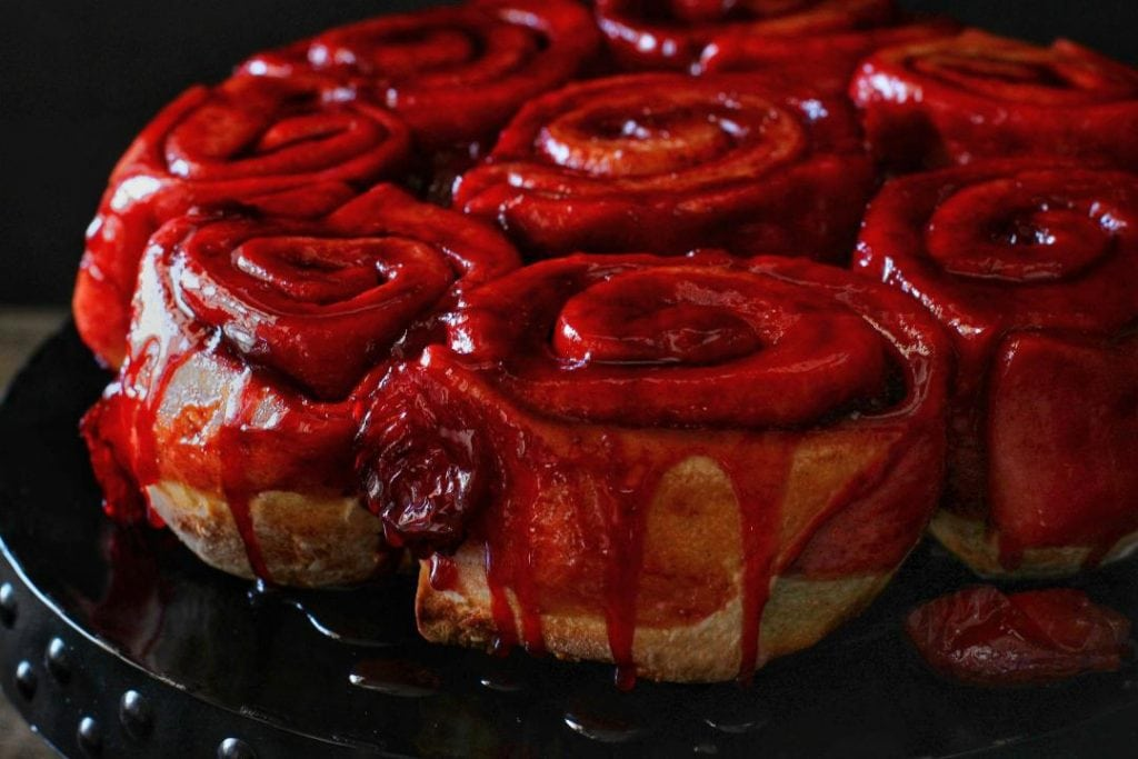 Sourdough Plum Cinnamon Rolls - Baked cinnamon rolls dripping with bright red plum juice on a black plate.