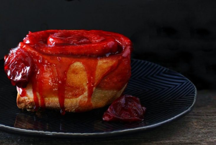 Sourdough Plum Cinnamon Rolls - A Baked cinnamon roll dripping with bright red plum juice on a black plate.