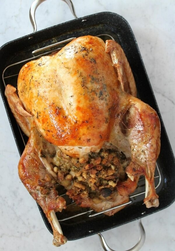 A beautiful fully cooked and stuffed in a black roasting pan.