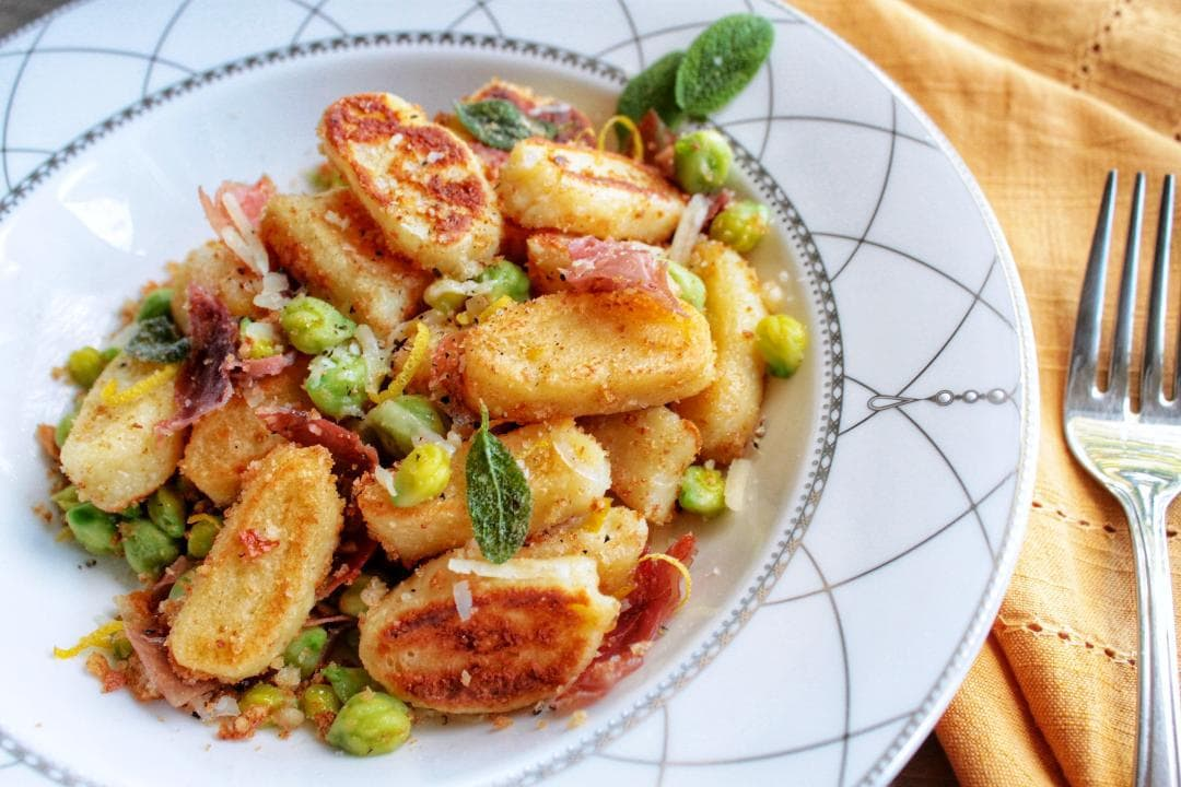 Pillowy soft Ricotta Gnocchi, or Gnudi served with sweet peas, crispy proscuitto, crunchy breadcrumbs, and accented with fresh sage. #Gnocchi #gnudi #pasta #dinner #comfortfood