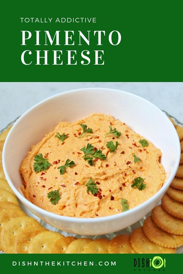 A white bowl containing orange Pimento Cheese dip surrounded by ritz crackers.
