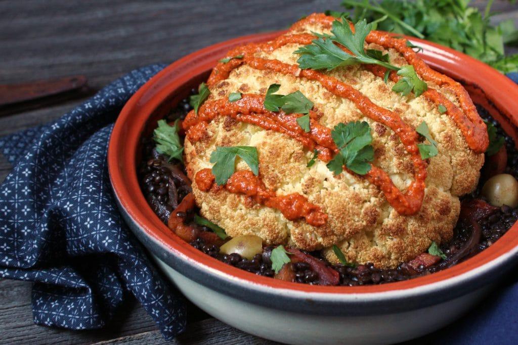 A white tajine holding a roasted whole cauliflower on a bed of lentil stew.