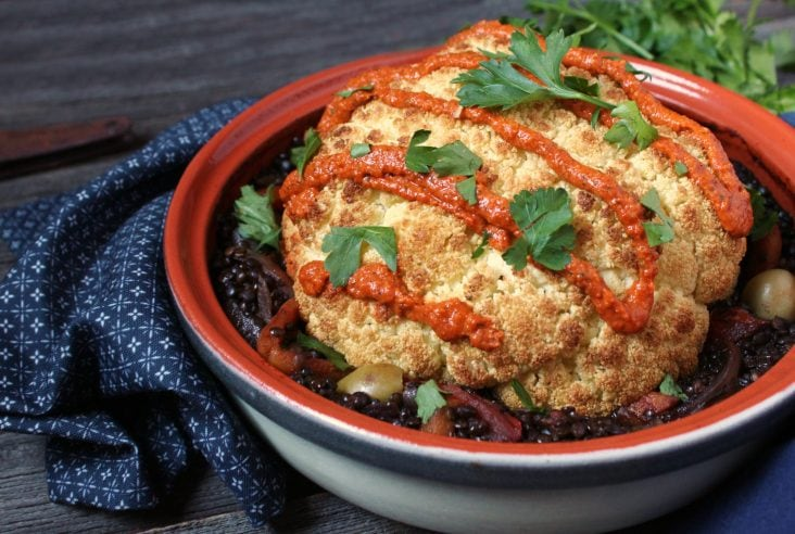A white tajine holding a roasted whole cauliflower on a bed of lentil stew.