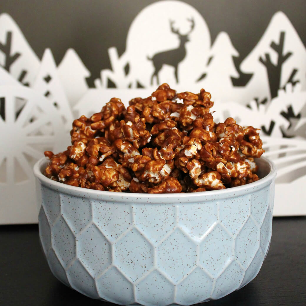 A bowl filled with Gingerbread Caramel Popcorn in front of a Winter scene.
