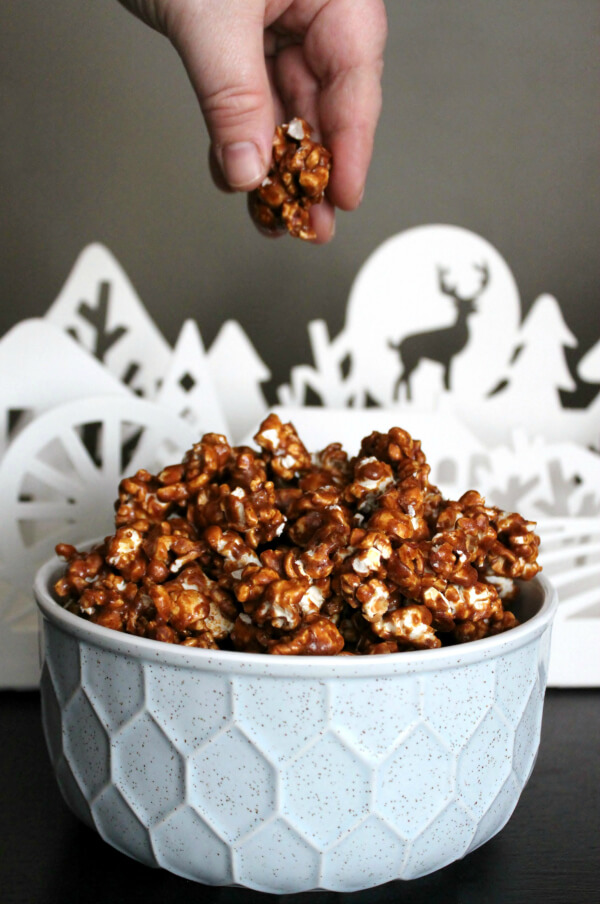 Gingerbread Caramel Popcorn A hand reaches for a handful of caramel popcorn out of a white dish.