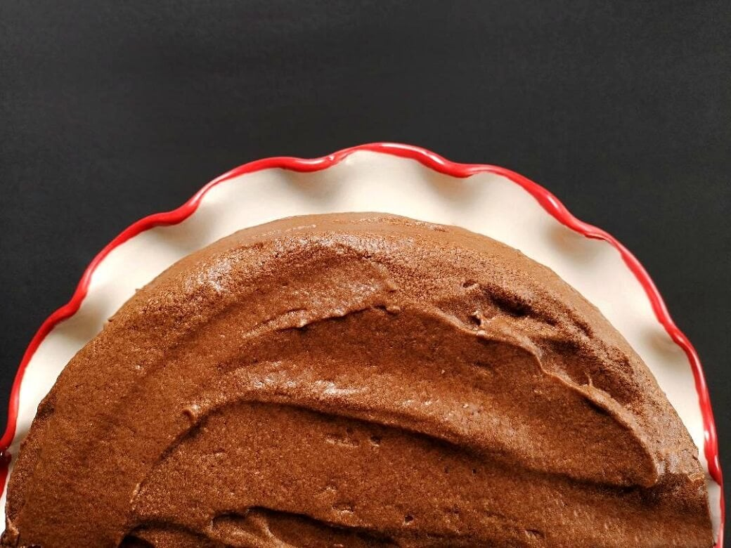 Overhead view of a half chocolate cake on a white plate with wavy red edges