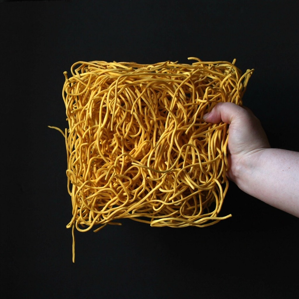 A hand holds a square bunch of dried noodles in front of a black background.