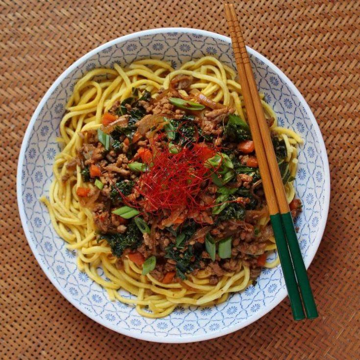 Szechuan Ground Pork Stir Fry - a bowl of noodles topped with ground pork stir fry, carrots, green onions, and kale.
