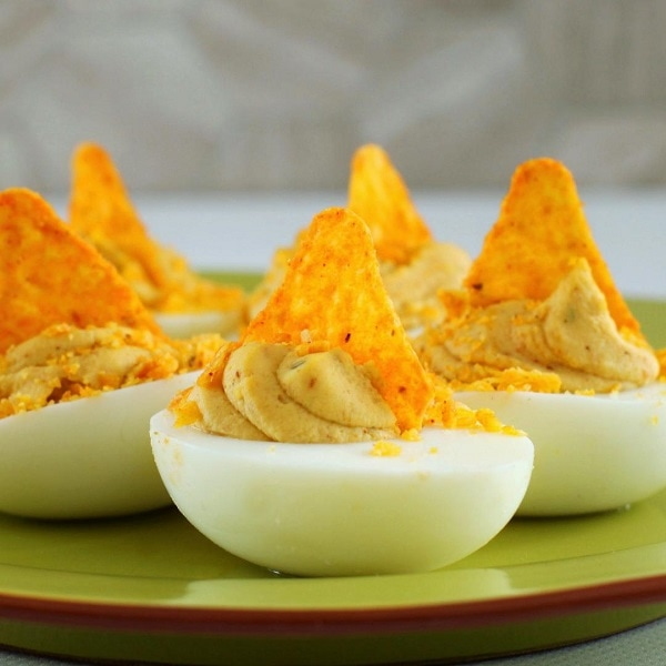 A dish of Nacho Deviled Eggs topped with Dorito crumbs.