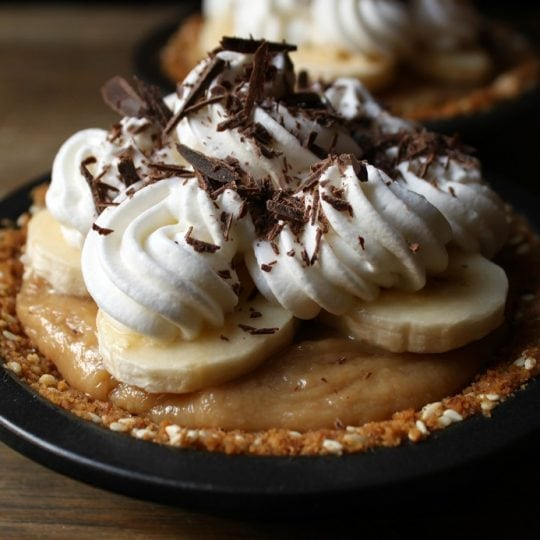 These mini Banoffee Pies feature the superb combination of bananas and caramel with a bit of rum thrown in for fun. The base has sesame seeds for a little nutty kick. For sweet tooths only! #banoffeepie #pie #banana #toffee #dessert
