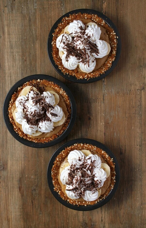 Three mini banoffee pies on a wooden background