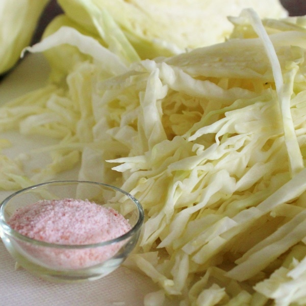 Sliced green cabbage with a small bowl of pink Himalayan salt.