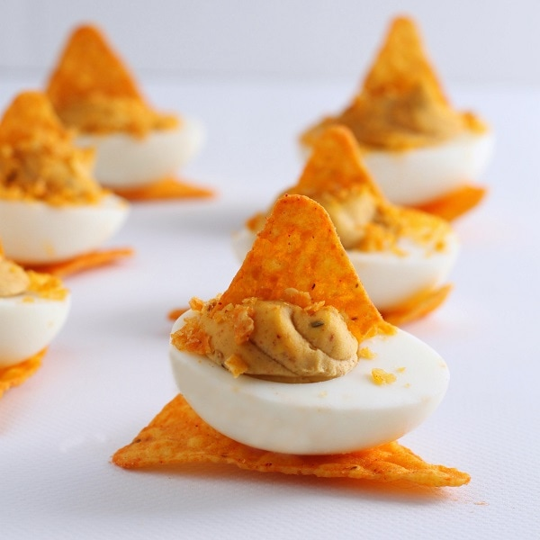 A group of Nacho Deviled Eggs topped with Dorito crumbs.