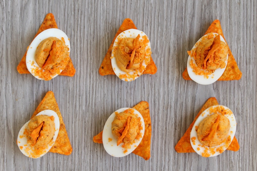 These Zesty Nacho Deviled Eggs have all the flavour of classic deviled eggs plus a kick of taco spice and the crunch of Dorito crumbs. Perfect for game day, potluck, or any family gathering. #deviledeggs #doritocrumb #nachoeggs #nachodeviledeggs