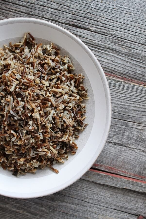 A vertical photo of half a bowl of cooked wild rice on a wooden background.