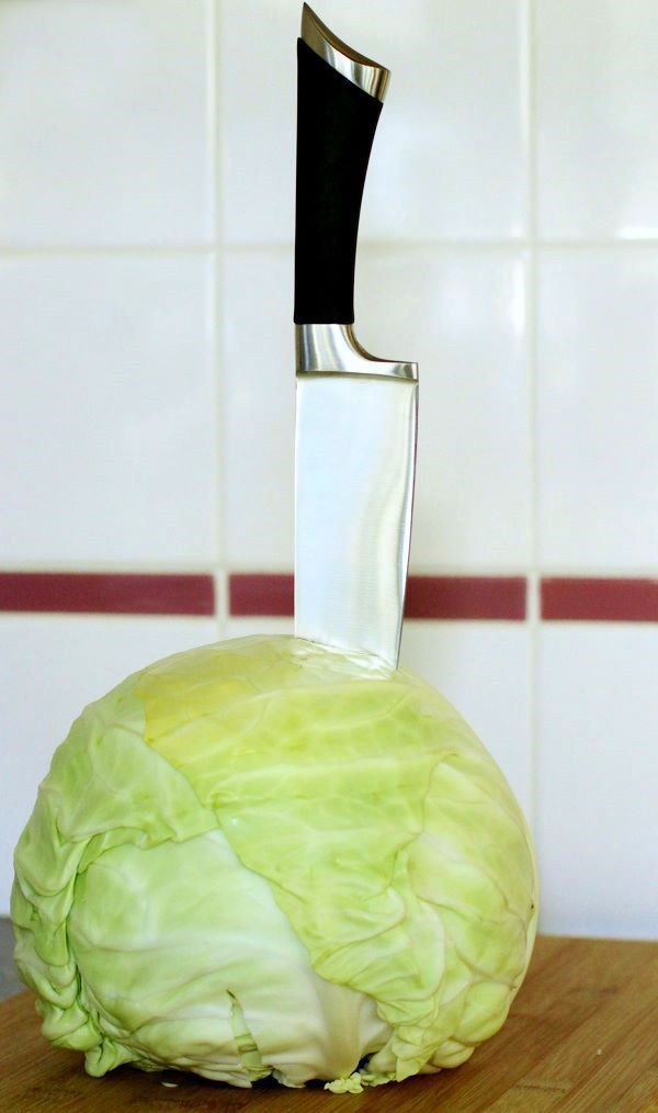 A whole green cabbage with a knife stuck in the top.