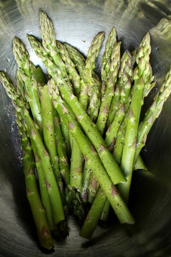 Green stalks of asparagus in a stainless steel bowl.