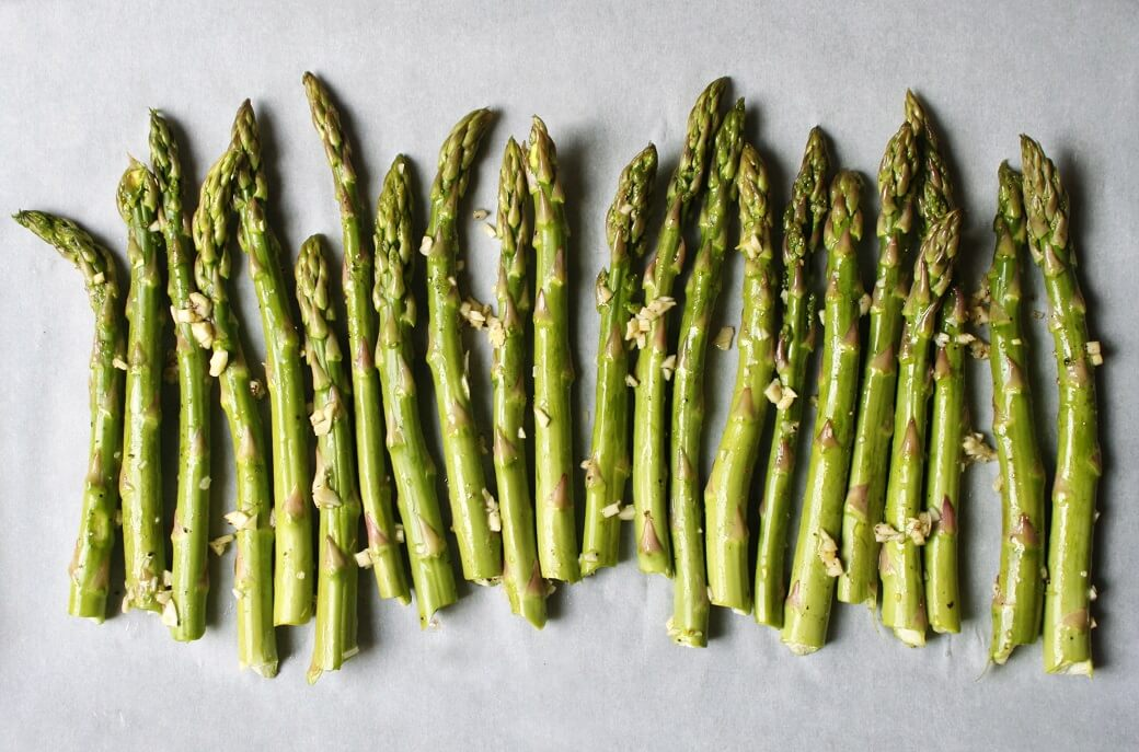 Green stalks of asparagus and minced garlic on parchment paper.