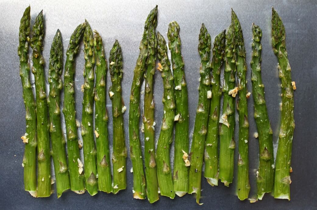 Roasted stalks of green asparagus on a baking tray.