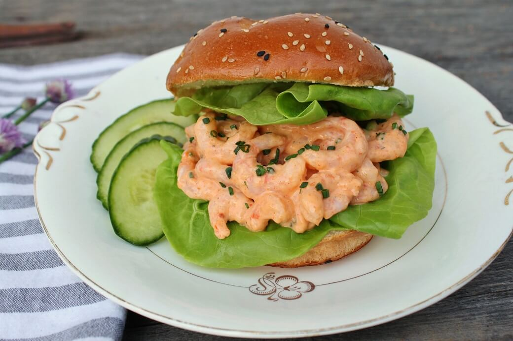 A Plate containing a seed topped bun filled with lettuce and shrimp mixed with rémoulade.