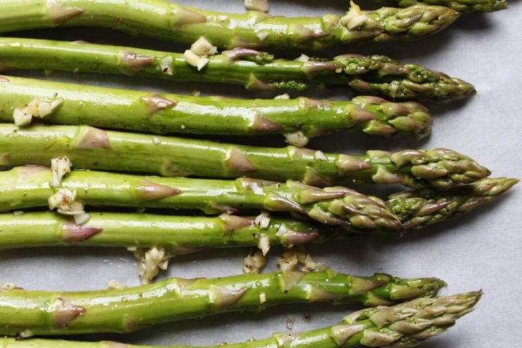 Close up photo of stalks of green asparagus and minced garlic.