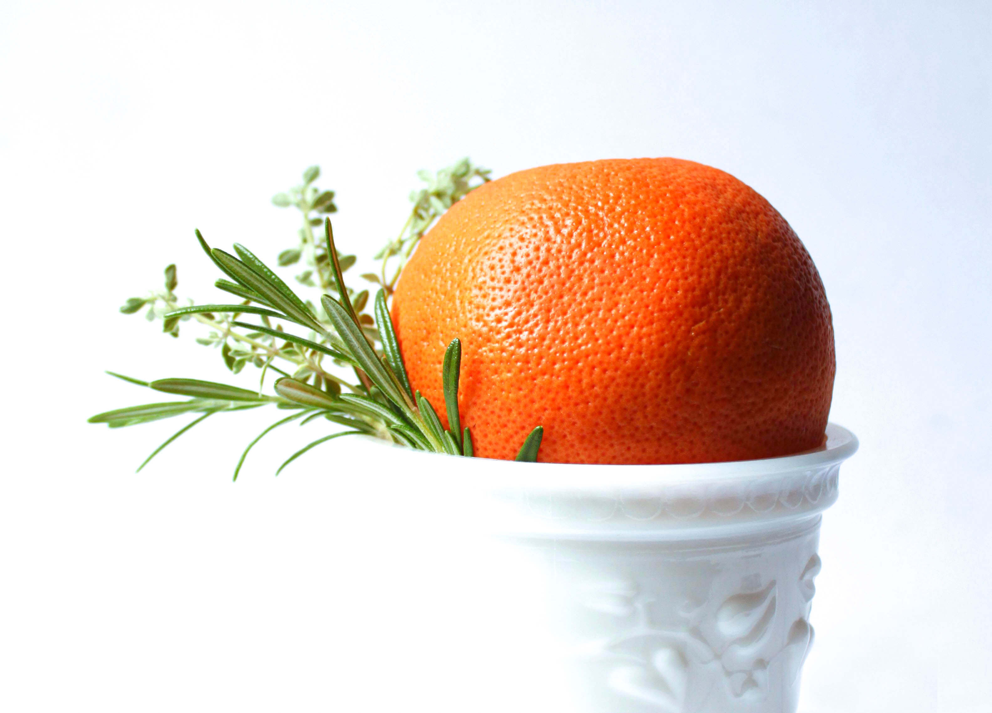 A bright orange in a white vase with fresh green herbs.