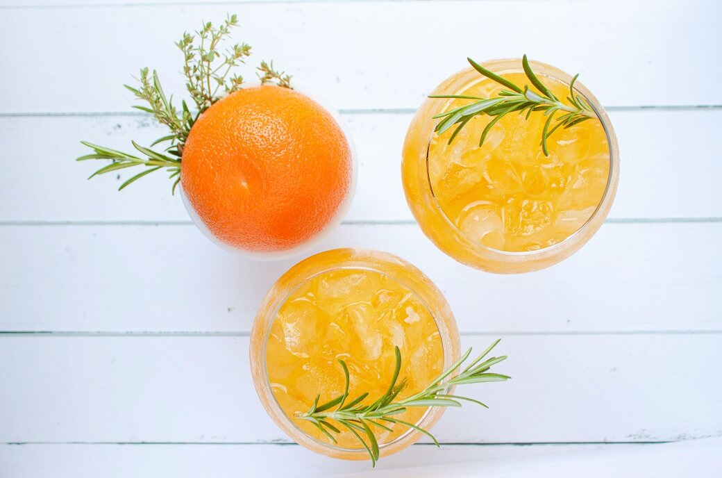 Two bright orange icy drinks garnished with fresh rosemary.