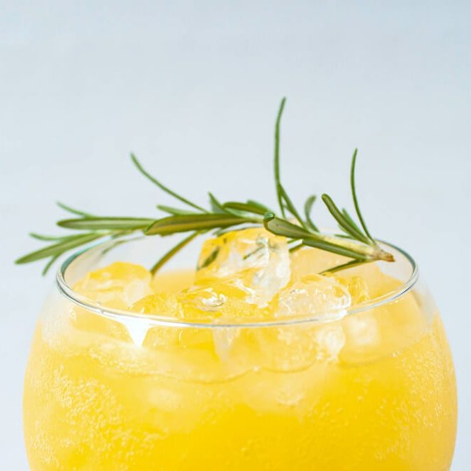 A single large wineglass containing an icy orange cocktail garnished with green rosemary.
