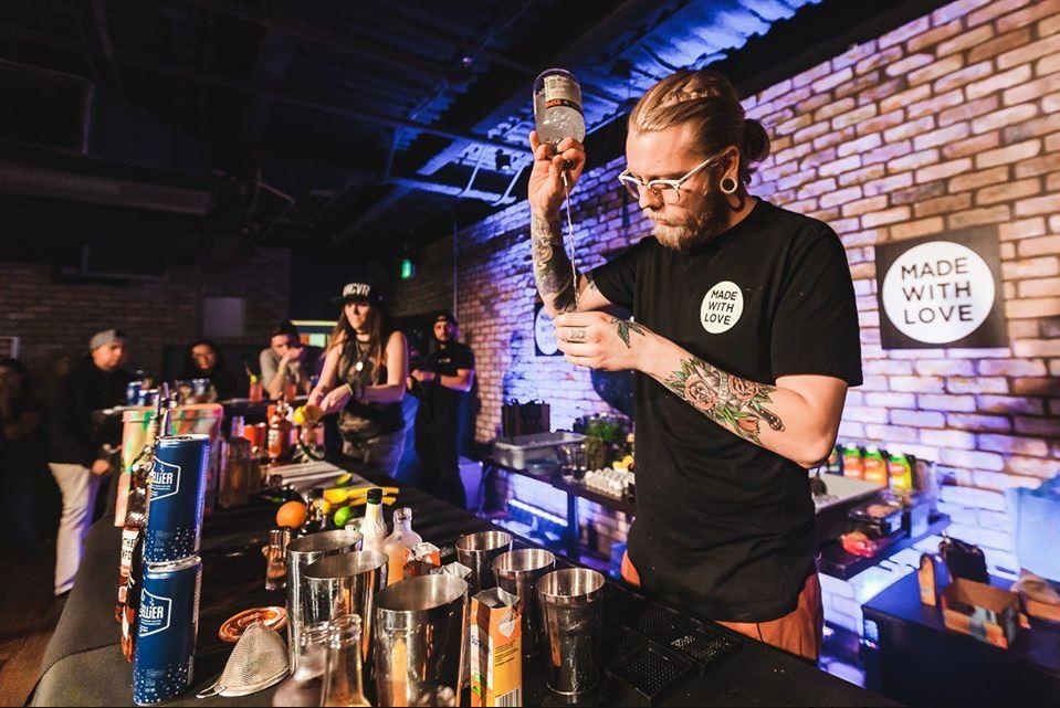A bartender pours out a cocktail from a cocktail shaker.