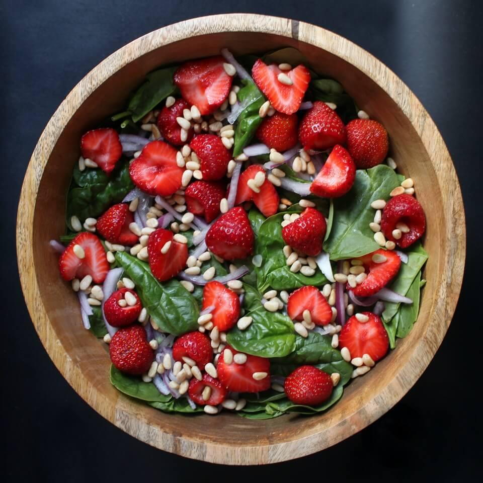 A wooden bowl containing green baby spinach, red strawberries, pine nuts and red onions.