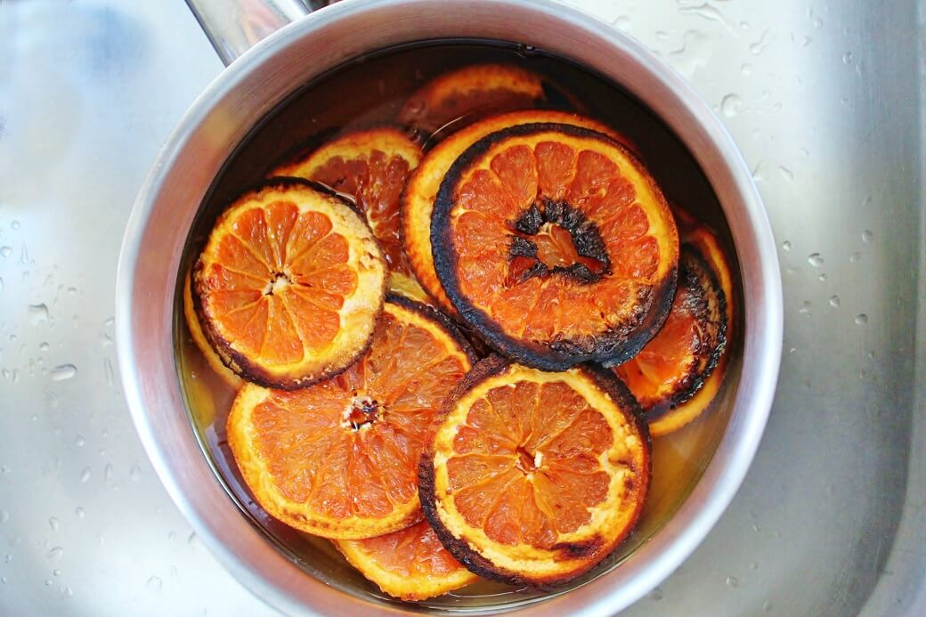 A saucepan filled with dark roasted orange slices.