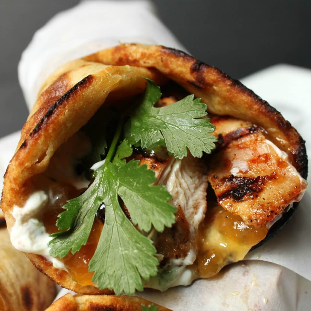 close up of grilled chicken wrapped in paratha along with cilantro, mango chutney, and raita.