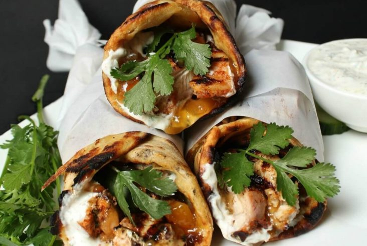 grilled chicken wrapped in paratha along with cilantro, mango chutney, and raita.