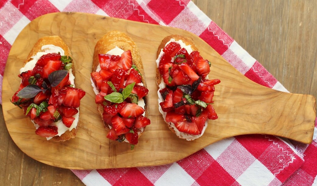 A wooden board holding three slices of baguette topped with red strawberries and green basil. Strawberry Basil Crostini