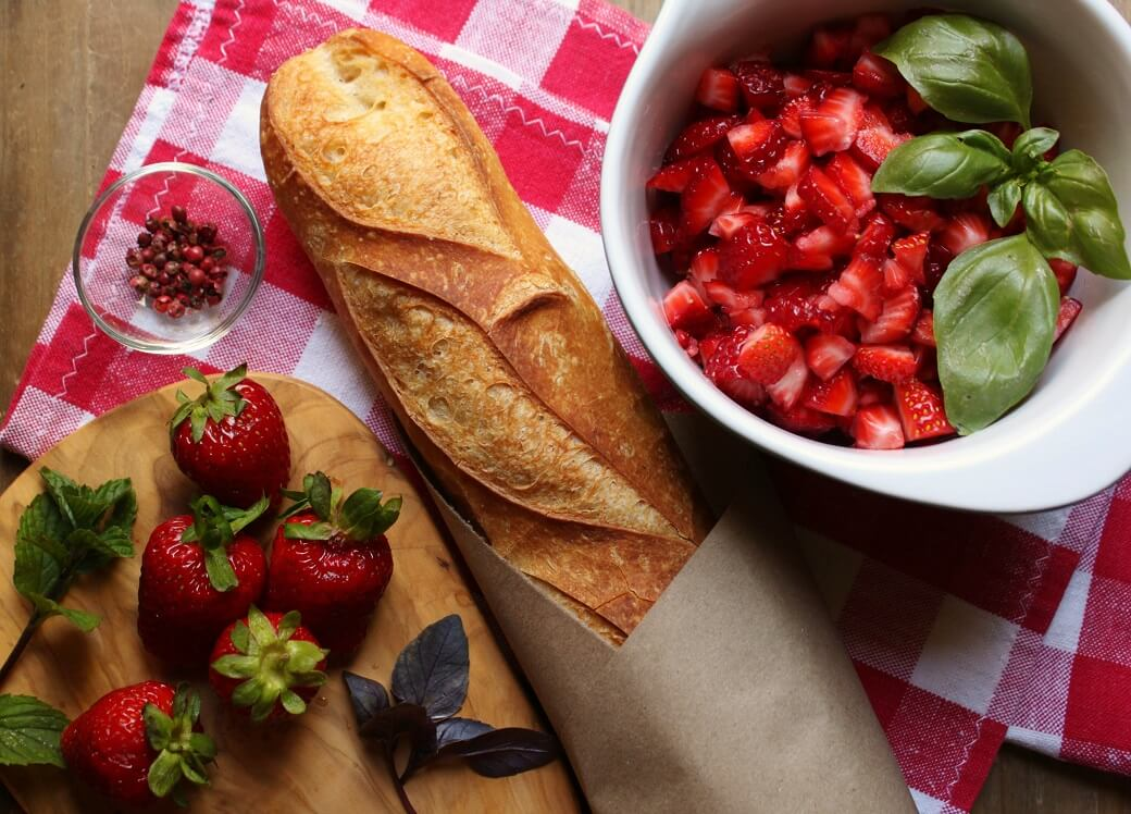 A bowl of chopped strawberries and basil beside a baguette and whole strawberries.