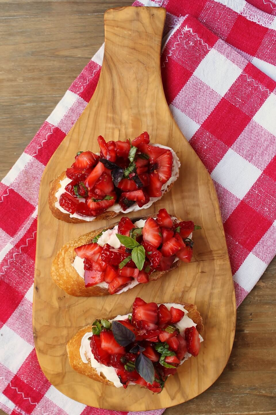 A wooden board holding Strawberry Basil Crostini: three slices of baguette topped with red strawberries and green basil.