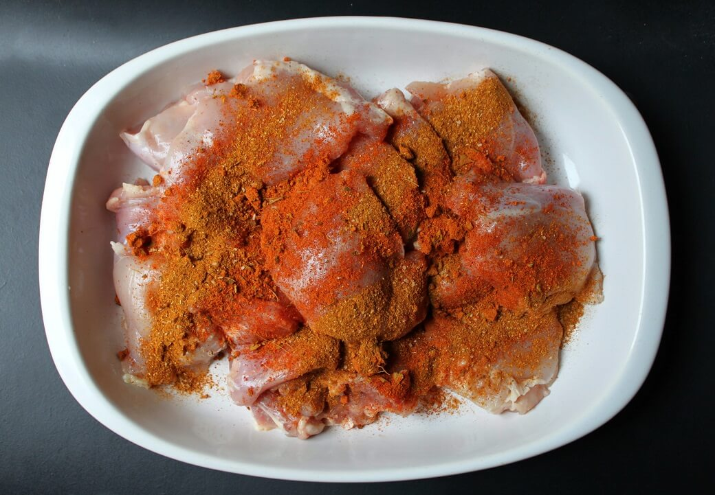 Raw chicken covered in bright orange spices