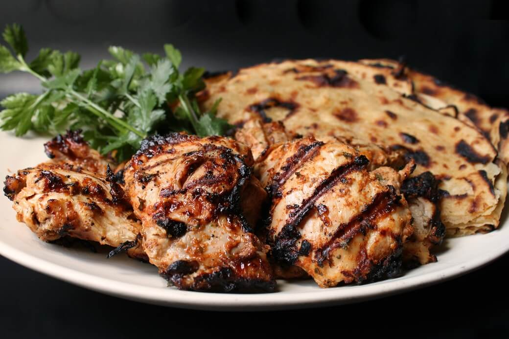 a white platter containing grilled chicken, paratha bread, and fresh cilantro.
