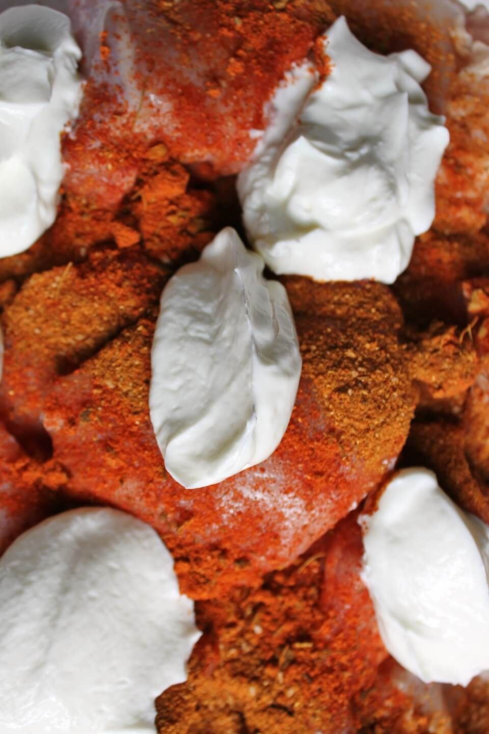 Raw chicken covered in bright orange spices and dotted with white yogurt.
