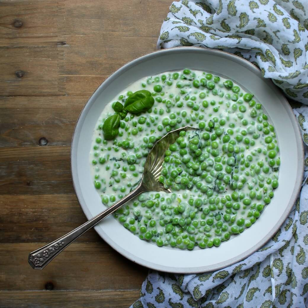A bowl of green peas in a creamy sauce sits on a wooden table surrounded by a napkin with a green paisley print.