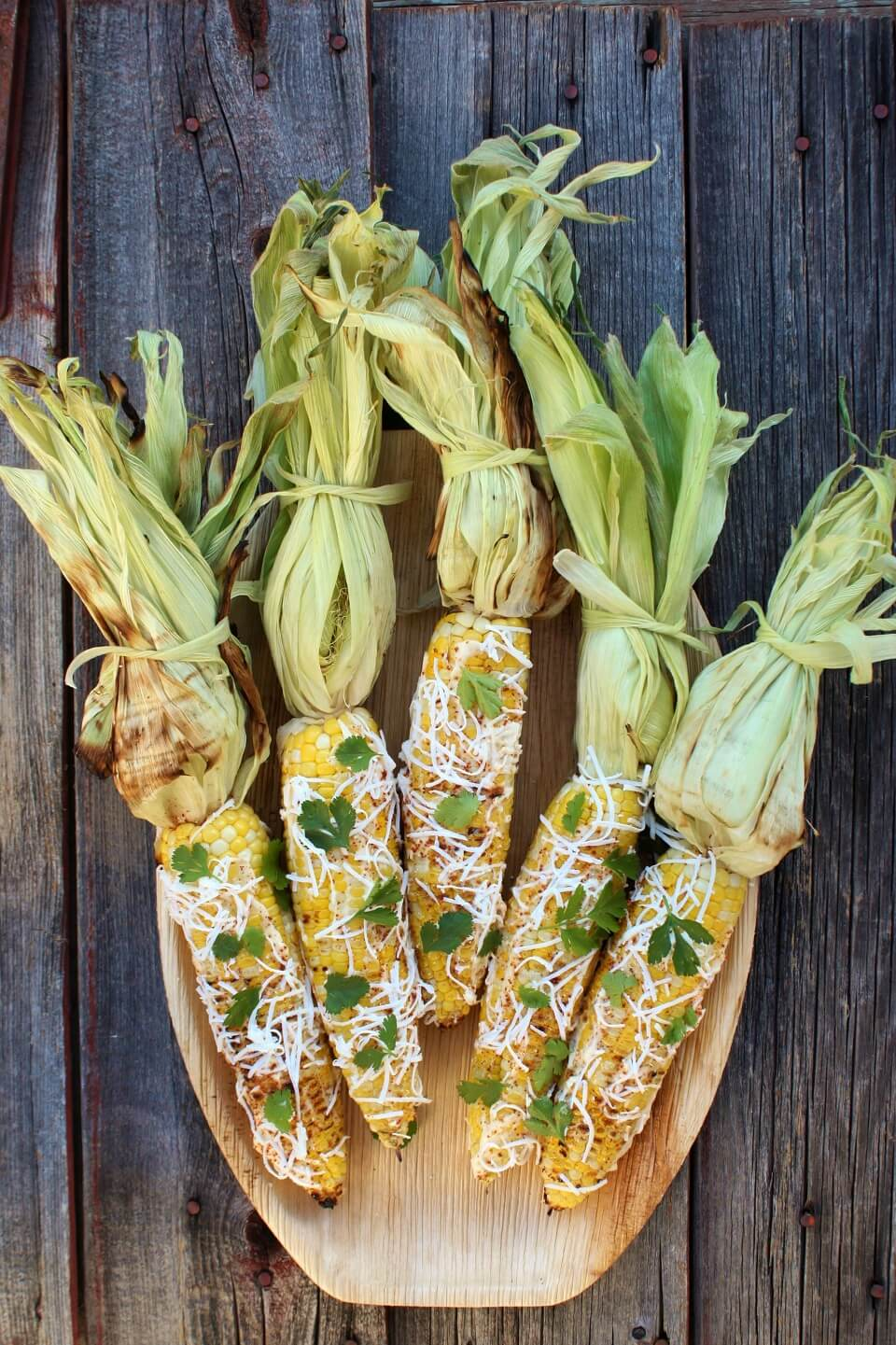 A wooden platter holding 5 yellow cobs of corn covered with mayonnaise and sprinkled with cheese, spices, and cilantro.