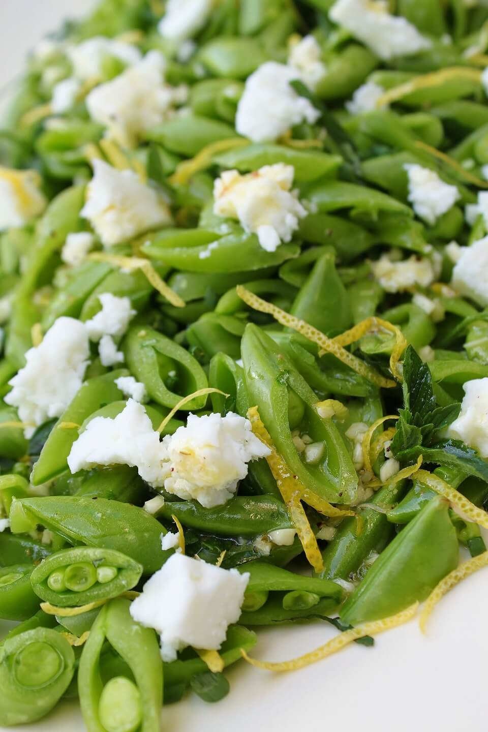 A close up of a bright green chopped snap pea salad with lemon zest, white feta, and herbs.