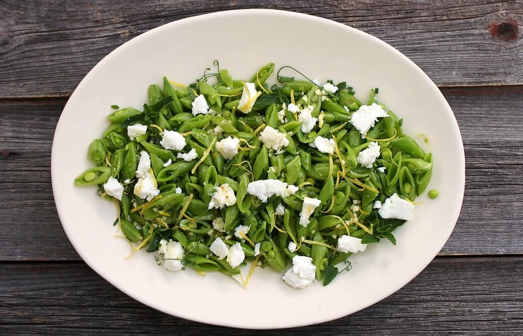 A white platter containing a bright green chopped snap pea salad, lemon zest, white feta, and herbs.