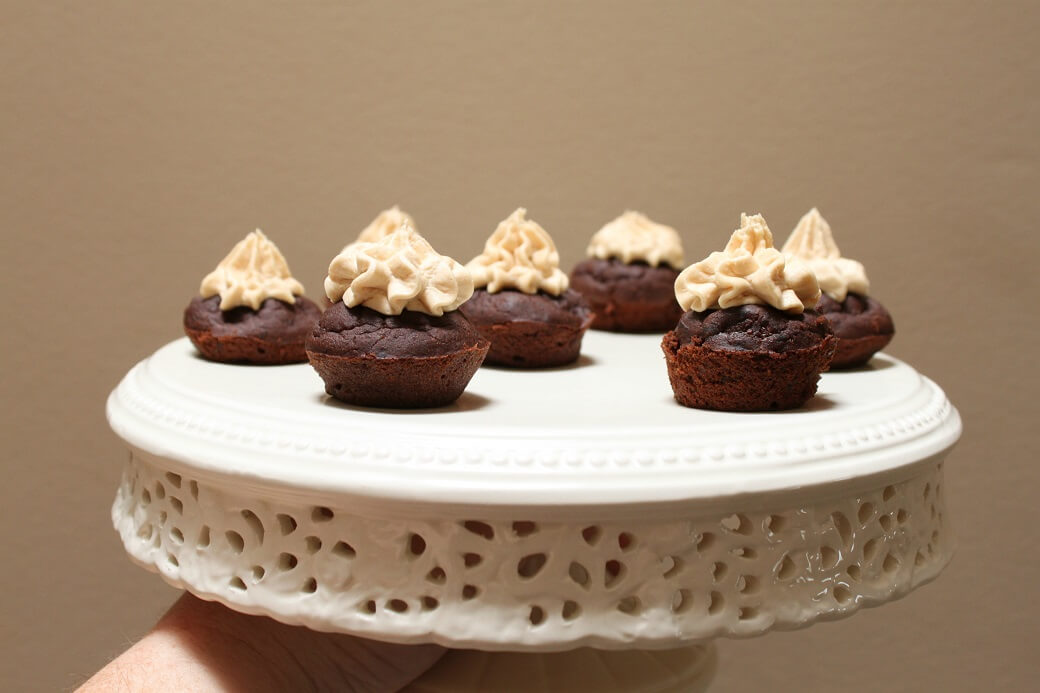 Seven bite sized black bean brownies topped with peanut butter frosting sit on a cream plate.
