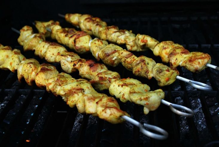 Cooked turmeric marinated Chicken kabobs on a grill.