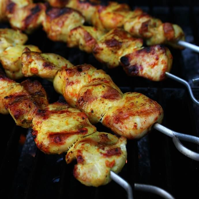 Cooked turmeric marinated Chicken skewers on a grill.