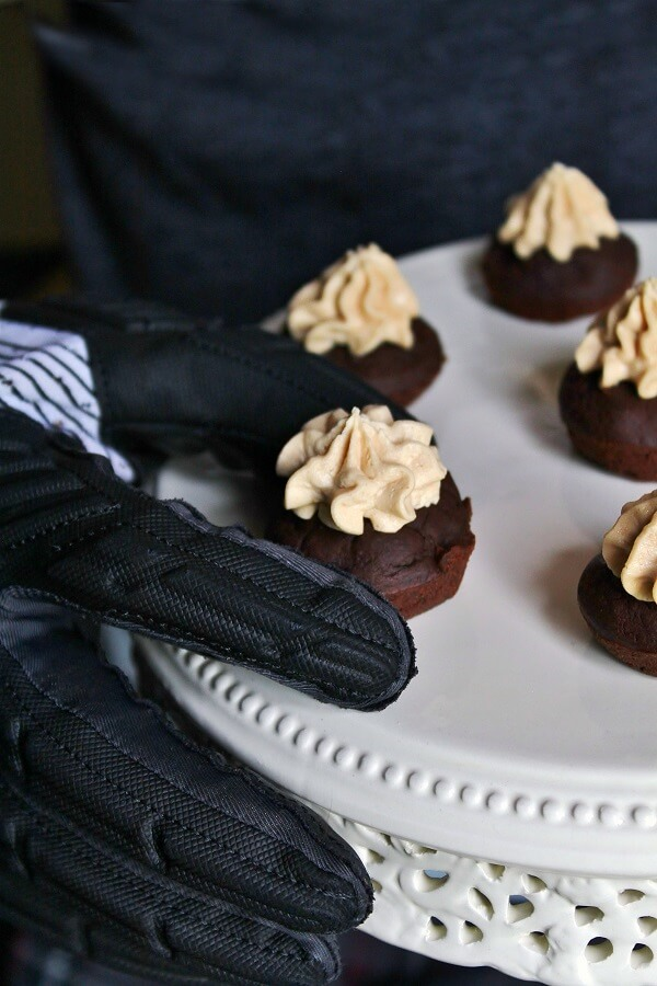A football glove covered hand reaches out for a bite sized black bean brownies topped with peanut butter frosting sitting on a cream plate.